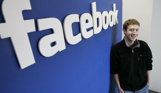 FILE - In this Monday, Feb. 5, 2007 file photo, Mark Zuckerberg poses for a photo next to a Facebook logo at the offices in Palo Alto, Calif. The social networking site is turing 15 on Monday, Feb. 4, 2019. (AP Photo/Paul Sakuma, File)