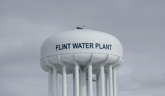 In this Feb. 26, 2016 photo, the Flint Water Plant tower is shown in Flint, Mich. Michigan Gov. Gretchen Whitmer is restructuring the state agency that drew criticism for its handling of the Flint water crisis under former Gov. Rick Snyder. (AP Photo/Paul Sancya)