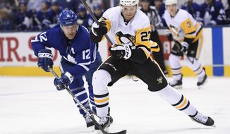 Toronto Maple Leafs center Patrick Marleau (12) and Pittsburgh Penguins center Nick Bjugstad (27) battle for the puck during the third period of an NHL hockey game, Saturday, Feb. 2, 2019 in Toronto. (Nathan Denette/The Canadian Press via AP)
