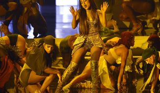 """FILE - In this Aug. 20, 2018, file photo, Ariana Grande, center, performs """"God is a woman"""" at the MTV Video Music Awards at Radio City Music Hall in New York. A Las Vegas artist is suing pop music star Grande, alleging federal copyright infringement over an image of a woman in a candle flame in the pop star's widely-viewed """"God is a Woman"""" music video. Representatives for Grande did not immediately respond Monday, Feb. 4, 2019, to messages about the lawsuit filed Thursday in U.S. District Court in Nevada by attorneys for Vladimir Kush and his company Kush Fine Arts Las Vegas. (Photo by Chris Pizzello/Invision/AP, File)"""