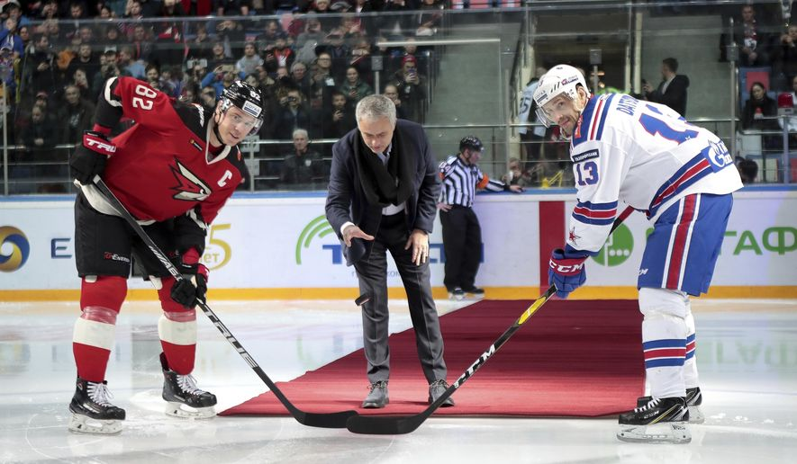 Former Manchester United coach Jose Mourinho, center, makes the first puck drop at Monday's Kontinental Hockey League game between Avangard Omsk and SKA St. Petersburg in Moscow, Russia, Monday, Feb. 4, 2019. Former Manchester United coach has ceremonially opened an ice hockey game in Russia _ and promptly fallen on the ice. (AP Photo/Dmitry Golubovich)
