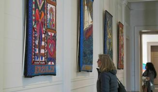 "Margot Wittig of Starnberg, Germany, foreground, and Amanda Fleury of Gretna, La., look at giant-sized sequined Vodou flags at the New Orleans Museum of Art on Wednesday, Jan. 30, 2018. The exhibit of work by Louisiana artist Tina Giruard and many Haitian bead artists at a studio in Haiti is titled ""Bondye: Between and Beyond"" and runs through June 16, 2019. (AP Photo/Janet McConnaughey)"