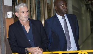 Former Australian soccer national team member Craig Foster, left, and Vice President of FIFPro Francis Awaritefe wait to meet detained Bahraini soccer player Hakeem al-Araibi as he arrives at the criminal court in Bangkok, Thailand, Monday, Feb. 4, 2019. Al-Araibi who has refugee status in Australia pleaded outside a Bangkok court on Monday for Thailand to not send him home to Bahrain, which is seeking his extradition to serve a prison sentence for a crime he denies. (AP Photo/Sakchai Lalit)