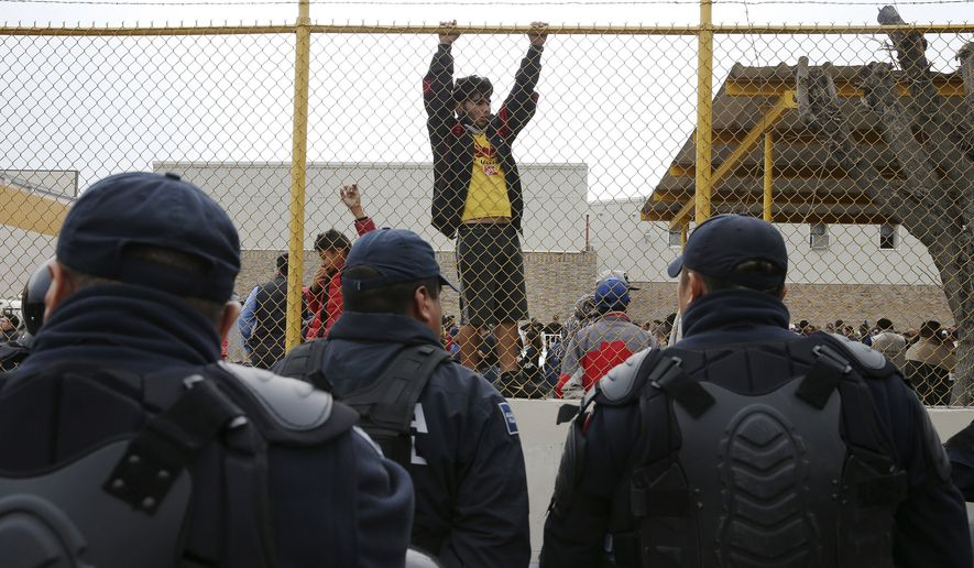"""Central American immigrants hang around by the fence line of a shelter guarded by Mexican Federal police in riot gear in Piedras Negras, Mexico, Tuesday, Feb. 5, 2019. A caravan of about 1,600 Central American migrants camped Tuesday in the Mexican border city of Piedras Negras, just west of Eagle Pass, Texas. The governor of the northern state of Coahuila described the migrants as """"asylum seekers,"""" suggesting all had express intentions of surrendering to U.S. authorities. (Jerry Lara/The San Antonio Express-News via AP)"""