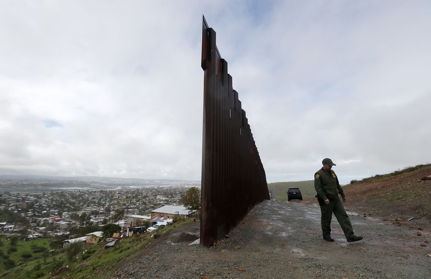 Border Patrol agent Vincent Pirro walks near where the border wall ends that separates Tijuana, Mexico, left, from San Diego, right, Tuesday, Feb. 5, 2019, in San Diego. President Donald Trump is expected to speak about funding for the wall along the U.S.-Mexico border during his State of the Union address Tuesday. (AP Photo/Gregory Bull)
