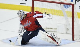 Washington Capitals goaltender Braden Holtby (70) reaches for the puck during the third period of an NHL hockey game against the Vancouver Canucks, Tuesday, Feb. 5, 2019, in Washington. The Capitals won 3-2. (AP Photo/Nick Wass) ** FILE **