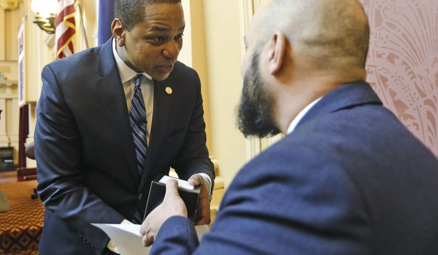 Virginia Lt. Gov. Justin Fairfax, left, greets Saifaldin Abdul Rahman, Dar Al Noor Islamic Center, Woodbridge, Va., after Rahman offered the prayer as the Senate session began at the Capitol in Richmond, Va., Tuesday, Feb. 5, 2019.  Fairfax, was confronted with an uncorroborated allegation of sexual misconduct first reported by a conservative website. Fairfax denied the allegation Monday and called it a political smear, telling reporters the 2004 encounter with a woman was consensual. (AP Photo/Steve Helber)