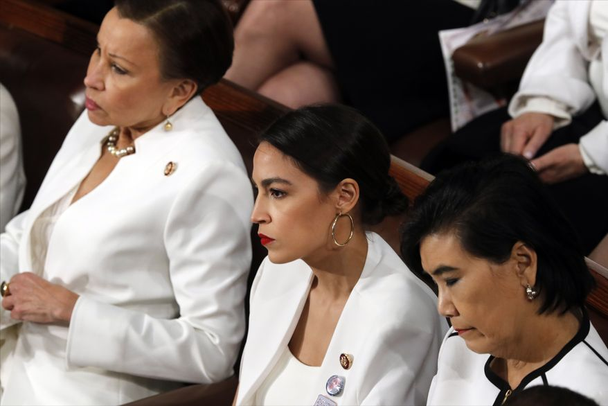 Rep. Alexandria Ocasio-Cortez, D-N.Y., center, listens as President Donald Trump delivers his State of the Union address to a joint session of Congress on Capitol Hill in Washington, Tuesday, Feb. 5, 2019. (AP Photo/J. Scott Applewhite)