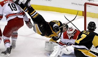 Pittsburgh Penguins' Garrett Wilson, center, is upended next to Carolina Hurricanes goaltender Curtis McElhinney, second from right, during the first period of an NHL hockey game in Pittsburgh, Tuesday, Feb. 5, 2019. (AP Photo/Gene J. Puskar)