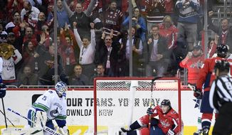 Washington Capitals right wing T.J. Oshie (77) celebrates his goal as Vancouver Canucks goaltender Jacob Markstrom (25), of Sweden, kneels on the ice during the first period of an NHL hockey game, Tuesday, Feb. 5, 2019, in Washington. (AP Photo/Nick Wass)