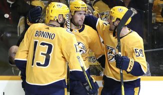 Nashville Predators' Filip Forsberg, center, of Sweden, is congratulated by Nick Bonino (13) and Roman Josi (59), of Switzerland, after Forsberg scored against the Arizona Coyotes during the second period of an NHL hockey game Tuesday, Feb. 5, 2019, in Nashville, Tenn. (AP Photo/Mark Humphrey)