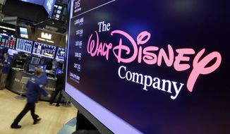 FILE- In this Monday, Aug. 7, 2017, file photo, the Walt Disney Co. logo appears on a screen above the floor of the New York Stock Exchange. The Walt Disney Co. reports financial results Tuesday, Feb. 5, 2019. (AP Photo/Richard Drew, File)