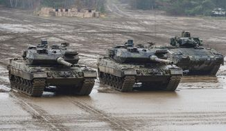 File--- Picture taken Dec.6, 2018 shows two Bundeswehr main battle tanks (from left), type Leopard 2A6 and a Puma infantry fighting vehicle, drive through the terrain during an exercise in Munster, Germany. (Philipp Schulze/dpa via AP)
