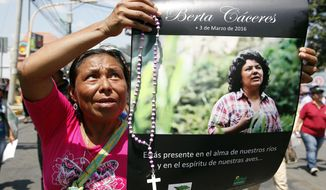 FILE - In this March 16, 2016 file photo, a woman holds up a poster with a photo of slain environmental leader Berta Caceres, during a protest march in Tegucigalpa, Honduras. Honduran prosecutors said on Tuesday, Feb. 5, 2019, that they plan to bring charges against Roberto David Castillo Mejia, a former executive who they allege was a mastermind behind the murder of environmental activist Berta Caceres. (AP Photo/Fernando Antonio, File)