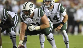 FILE - In this Aug. 16, 2018, file photo, New York Jets quarterback Sam Darnold (14) stands behind center Spencer Long (61) during the first half of a preseason NFL football game against the Washington Redskins in Landover, Md. The New York Jets have released offensive lineman Spencer Long, saving the team almost $6.5 million on next season's salary cap. Long was due a $3 million roster bonus that would have become guaranteed Wednesday, Feb. 6, 2019. The Jets opted instead to cut him Tuesday, Feb. 5, 2019 after he struggled with injuries and consistency at center before moving to left guard.  (AP Photo/Nick Wass, File)