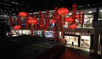 Decorations, part of a Lunar New Year installation, are placed in the main atrium of a mall Thursday, Jan. 31, 2019 in Santa Monica, Calif. In recent years, the Lunar or Chinese New Year, which people around the globe are ringing in Tuesday, seems to have achieved all-American status.  Major companies are celebrating  and capitalizing on a holiday that at its heart is about being with loved ones and wishing for prosperity and good luck.  (AP Photo/Marcio Jose Sanchez)