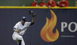 FILE - In this Sept. 18, 2018 file photo, Milwaukee Brewers' Curtis Granderson raises his glove after making a sliding catch in the outfield during the fifth inning of a baseball game against the Cincinnati Reds in Milwaukee. Granderson has agreed to a minor league contract with the Miami Marlins and will report to big league spring training.If added to the 40-man roster, he would get a one-year contract that pays $1.75 million while in the major leagues and have the chance to earn $250,000 in performance bonuses for plate appearances. (AP Photo/Aaron Gash, File)