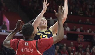 Michigan forward Ignas Brazdeikis (13) drives to the basket as Rutgers guard Montez Mathis (23) defends during the first half of an NCAA college basketball game Tuesday, Feb. 5, 2019, in Piscataway, N.J. (AP Photo/Bill Kostroun)