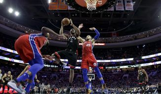 Toronto Raptors' Kawhi Leonard, center, goes up for a shot between Philadelphia 76ers' Ben Simmons, right, and Joel Embiid during the second half of an NBA basketball game, Tuesday, Feb. 5, 2019, in Philadelphia. Toronto won 119-107. (AP Photo/Matt Slocum)