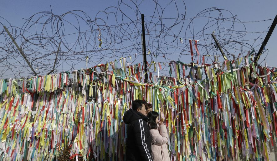A South Korean family pose in front of ribbons placed on a barbed wire fence with messages wishing for the reunification of the two Koreas as they visit the border to celebrate the Lunar New Year at the Imjingak Pavilion, near the demilitarized zone of Panmunjom, in Paju, South Korea, Tuesday, Feb. 5, 2019. (AP Photo/Ahn Young-joon) **FILE**