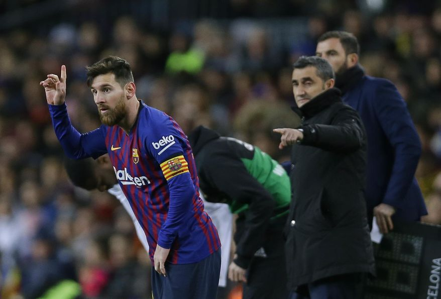 FC Barcelona's Lionel Messi, left, gestures next to his coach Ernesto Valverde during the Spanish La Liga soccer match between FC Barcelona and Valencia at the Camp Nou stadium in Barcelona, Spain, Saturday, Feb. 2, 2019. (AP Photo/Manu Fernandez)