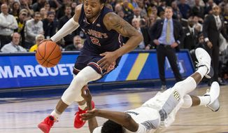 St. John's guard Shamorie Ponds, left, drives past Marquette forward Sacar Anim during the second half of an NCAA college basketball game Tuesday, Feb. 5, 2019, in Milwaukee. (AP Photo/Darren Hauck)