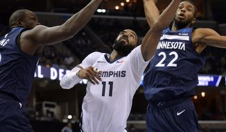 Memphis Grizzlies guard Mike Conley, center, shoots between Minnesota Timberwolves forward Andrew Wiggins, right, and Luol Deng, left, in the second half of an NBA basketball game Tuesday, Feb. 5, 2019, in Memphis, Tenn. (AP Photo/Brandon Dill)