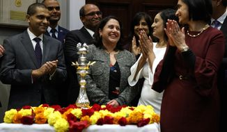 In this Nov. 13, 2018, file photo, Neomi Rao, administrator of the Office of Information and Regulatory Affairs, center, smiles as President Donald Trump announces his intention to nominate her to fill Brett Kavanaugh's seat on the U.S. Court of Appeals for the D.C. Circuit, during a Diwali ceremonial lighting of the Diya in the Roosevelt Room of the White House in Washington. (AP Photo/Evan Vucci, File)