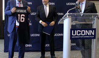 Thomas C. Katsouleas, left, is presented with a UConn basketball jersey by University of Connecticut Board of Trustees chairman Thomas Kruger, center, and Connecticut Gov. Ned Lamont after being appointed as the University of Connecticut's 16th president on Tuesday, Feb. 5, 2019 in Storrs, Conn. (AP Photo/Pat Eaton-Robb)