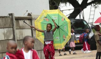 A child plays with an umbrella bearing the portrait of Zimbabwean President Emmerson Mnangagwa, at a public school in Harare, Tuesday, Feb. 5, 2019. Zimbabwe's public teachers are alleging intimidation as they try to launch a nationwide strike for better salaries. (AP Photo/Tsvangirayi Mukwazhi)