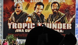 """A worker cleans inside the hotel before the arrival of U.S. actor and film director, Ben Stiller, and U.S. actor Robert Downey in front of a giant banner promoting their new film, ''Tropic Thunder,"""" at the 56th San Sebastian Film Festival in San Sebastian, northern Spain, Saturday, Sept. 20, 2008. The San Sebastian Film Festival, the oldest and most prestigious in the Spanish speaking World, opens with a strong focus on European and U.S. movies. (AP Photo/Alvaro Barrientos) ** FILE **"""