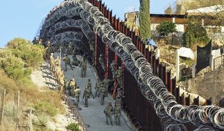 In this Saturday, Feb. 2, 2019, photo, U.S. Army troops place additional concertina wire to the border fence on a hillside above Nelson Street in downtown Nogales, Ariz. (Jonathan Clark/Nogales International via AP) ** FILE **