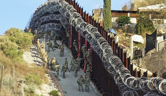 In this Saturday, Feb. 2, 2019 photo, U.S. Army troops place additional concertina wire to the border fence on a hillside above Nelson Street in downtown Nogales, Ariz. Nogales, Mexico is seen at right. The small Arizona border city is fighting back against the installation of razor fencing that now covers the entirety of a tall border fence along the city's downtown area. The city of Nogales, which sits on the border with Nogales, Mexico, is contemplating a proclamation Wednesday, Feb. 6, 2019, condemning the use of concertina wire in its town. (Jonathan Clark/Nogales International via AP)