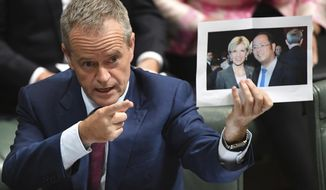 In this June 14, 2017, photo, leader of the opposition party Bill Shorten holds a photograph of Minister for Foreign Affairs Julie Bishop and Chinese businessman Huang Xiangmo during Question Time in the House of Representatives at Parliament House in Canberra, Australia. Australia has cancelled the residency of Huang but the foreign minister says she doesn't expect Beijing to protest. (Mick Tsikas/AAP Image via AP)