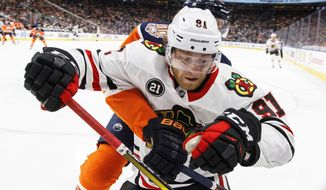 Chicago Blackhawks' Drake Caggiula (91) battles in the corner with Edmonton Oilers' Kris Russell during the first period of an NHL hockey game Tuesday, Feb. 5, 2019, in Edmonton, Alberta. (Jason Franson/The Canadian Press via AP)