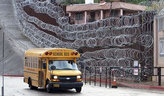 In this Monday, Feb. 4, 2019 photo, a school bus rolls past the concertina wire-covered fence at East International and Nelson Streets in downtown Nogales, Ariz. The small Arizona border city is fighting back against the installation of razor fencing that now covers the entirety of a tall border fence along the city's downtown area. The city of Nogales, which sits on the border with Nogales, Mexico, is contemplating a proclamation Wednesday, Feb. 6, 2019, condemning the use of concertina wire in its town. (Jonathan Clark/Nogales International via AP)