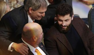 Former Cleveland Browns quarterback Bernie Kosar, top, talks with quarterback Baker Mayfield, right, and coach Freddie Kitchens at the Cleveland Sports Awards, Wednesday, Feb. 6, 2019, in Cleveland. Mayfield, who finished second to New York Giants running back Saquon Barkley for Offensive Rookie of the Year, is expected to win male athlete of the year at the Cleveland Sports Awards. (AP Photo/Tony Dejak)