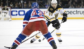 Boston Bruins center Patrice Bergeron (37) skates against New York Rangers defenseman Brendan Smith (42) in the first period of an NHL hockey game, Wednesday, Feb. 6, 2019, at Madison Square Garden in New York. (AP Photo/Mary Altaffer)