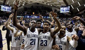 Villanova's Dhamir Cosby-Roundtree (21), Jermaine Samuels (23) and Phil Booth (5) celebrate after the team's NCAA college basketball game against Creighton, Wednesday, Feb. 6, 2019, in Villanova, Pa. Villanova won 66-59 in overtime. (AP Photo/Matt Slocum)