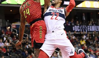 Atlanta Hawks guard Kent Bazemore (24) fouls Washington Wizards forward Otto Porter Jr. (22) as he goes to the basket during the second half of an NBA basketball game, Monday, Feb. 4, 2019, in Washington. The Hawks won 137-129. (AP Photo/Nick Wass)