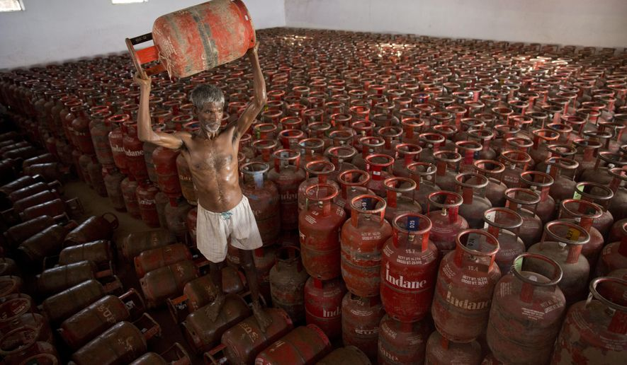 FILE- In this Aug.1, 2016 file photo, an Indian laborer sorts liquefied petroleum gas (LPG) cylinders used for cooking at a warehouse after downloading them from a truck in Allahabad, India.  India has become the world's second largest importer of liquefied petroleum gas as its government pushes cleaner alternatives to traditional cooking fuels such as firewood and cow dung. (AP Photo/Rajesh Kumar Singh, File)