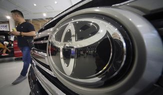 FILE - In this Aug. 3, 2018, file photo, a visitor walks through a Toyota showroom in Tokyo. Toyota Motor Corp. said Wednesday, Feb. 6, 2019 its fiscal third quarter profit plunged to 180.9 billion yen ($12.6 billion), about a fifth of what the Japanese automaker earned the previous year, despite relatively solid sales. (AP Photo/Eugene Hoshiko, File)