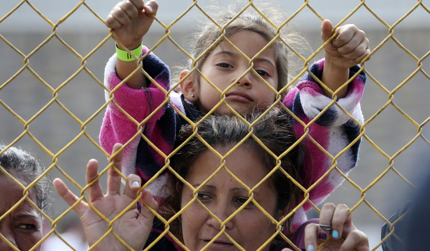 """Six-year-old Daniela Fernanda Portillo Burgos sits on the shoulders of her mother, Iris Jamilet, 39, as they look out through the fence of a immigrant shelter in Piedras Negras, Mexico, Tuesday, Feb. 5, 2019. A caravan of about 1,600 Central American migrants camped Tuesday in the Mexican border city of Piedras Negras, just west of Eagle Pass, Texas. The governor of the northern state of Coahuila described the migrants as """"asylum seekers,"""" suggesting all had express intentions of surrendering to U.S. authorities. (Jerry Lara/The San Antonio Express-News via AP)"""