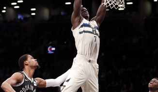 FILE - In this Feb. 4, 2018, file photo, Brooklyn Nets forward James Webb III (0) watches as Milwaukee Bucks center Thon Maker (7) dunks over him during the first half of an NBA basketball game, in New York. A person familiar with the situation says the NBA-leading Milwaukee Bucks have agreed to trade center Thon Maker to the Detroit Pistons for forward Stanley Johnson. The person spoke to The Associated Press Wednesday, Feb. 6, 2019, on condition of anonymity because the deal had not been publicly announced.(AP Photo/Kathy Willens, File)