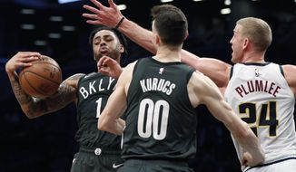 Brooklyn Nets guard D'Angelo Russell (1) pulls down a rebound in front of Denver Nuggets forward Mason Plumlee (24) as Nets forward Rodions Kurucs (00) watches during the first half of an NBA basketball game Wednesday, Feb. 6, 2019, in New York. (AP Photo/Kathy Willens)