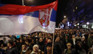 FILE - In this file photo dated Saturday, Feb. 2, 2019, people march during a protest against populist President Aleksandar Vucic in Belgrade, Serbia. Serbia's Prime Minister Ana Brnabic has rejected an independent democratic freedom watchdog's report that downgraded the Balkan country from ''free'' to ''partly free.'' (AP Photo/Darko Vojinovic, FILE)