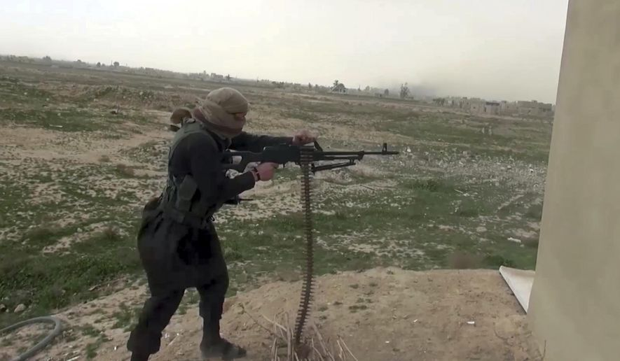This frame grab from video posted online Friday, Jan. 18, 2019, by supporters of the Islamic State group, purports to show an ISIS fighter firing a weapon during clashes with members of the U.S.-backed Syrian Democratic Forces, in the eastern Syrian province of Deir el-Zour, Syria. (Militant Photo via AP) ** FILE **