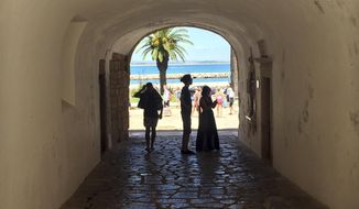 In this June, 27, 2018 photo, tourists walk through a tunnel at the medieval-area Castle of Lagos in Lagos, Portugal. Lagos, a striking Portuguese beach town of charming coastlines and slightly sandstone cliffs, is the birthplace of the African slave trade in Europe. A museum dedicated to slavery is helping this enclave in the heart of southern Portugal's Algarve region come to terms with its history. (AP Photo/Russell Contreras)