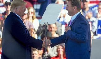 "FILE - In this Oct. 20, 2018, file photo, President Donald Trump and U.S. Sen. Dean Heller, R-Nev., shake hands at a campaign rally in Elko, Nev. President Trump says former Nevada Sen. Heller lost his re-election because he was ""extremely hostile"" to Trump during the 2016 election and that he didn't pick Heller to be U.S. Interior Secretary because he couldn't get his base excited about the Republican, the Las Vegas Review-Journal reports. (AP Photo/Alex Goodlett, File)"
