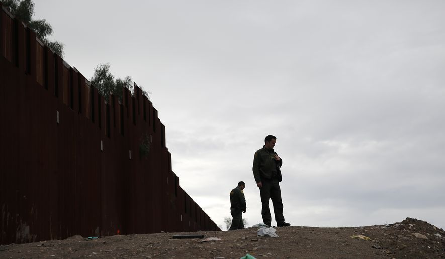 In this Jan 15, 2019, image, U.S. Border Patrol agents look on in front of a section of newly replaced border wall in San Diego. (AP Photo/Gregory Bull) **FILE**